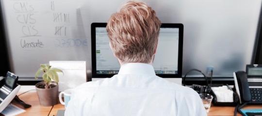 Henrik Banneck prüft eine Freelancer Rechnung am Computer