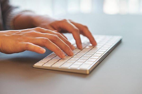 Hände eines IT Freelancers tippen auf Tastatur