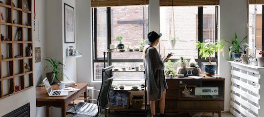 Junge Freelancerin in einer Wohnung macht sich Gedanken zum Selbstmarketing