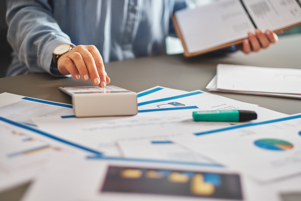 Finanzen Freelancer bei der Arbeit am Schreibtisch mit Taschenrechner