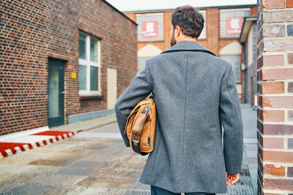 Freelancer Restrukturierung mit Aktentasche unterm Arm auf dem Weg zur Arbeit