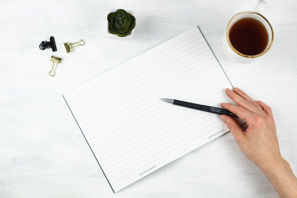 Vorbereitung auf die Gehaltsverhandlung als Freelancer mit Block und Stift